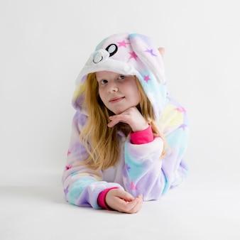 Linda loira posando de branco em pijama kigurumi, fantasia de coelho