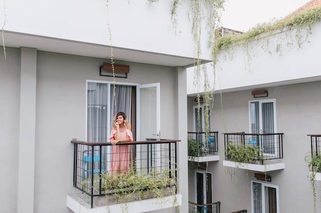 Linda loira posando na varanda do hotel. sorridente mulher romântica em vestido rosa, aproveitando a manhã.