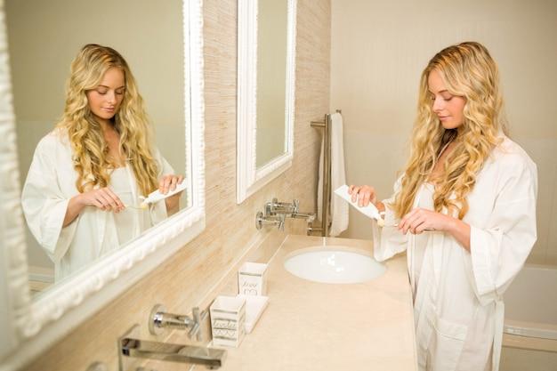 Linda loira prestes a escovar os dentes no banheiro