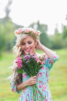 Linda loira segurando um buquê de flores na zona rural.