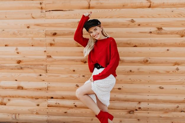 Linda loira sendo louca e engraçada na parede de madeira. mulher bonita em um vestido branco moderno, tendo um grande momento ao ar livre.