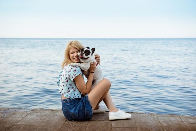 Linda loira sentada, brincando com bulldog francês perto do mar