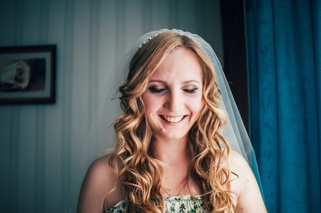 Linda loira sorridente com cabelos cacheados. vestido branco de verde.