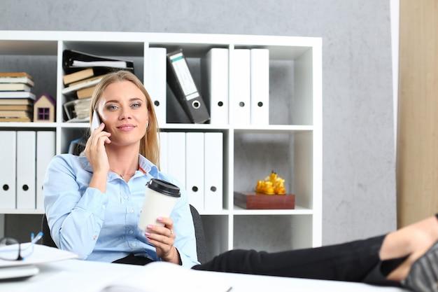 Linda loira sorridente empresária fala celular no retrato de escritório.