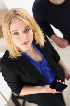 Linda loira sorridente empresária segurando