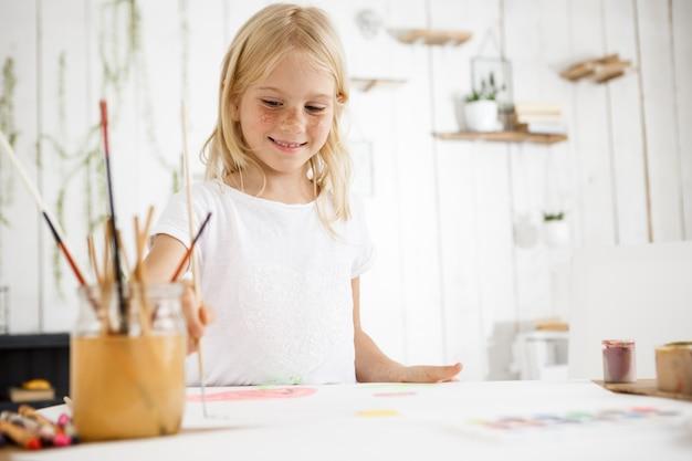 Linda loira sorrindo e alegremente pintando imagens com pincel