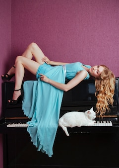 Linda loira tocando piano com um gato