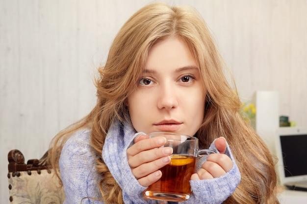 Linda loira tomando chá com limão em casa