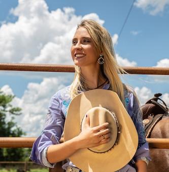 Linda loira vaqueira com chapéu de pé perto do fundo de rancho de cavalo