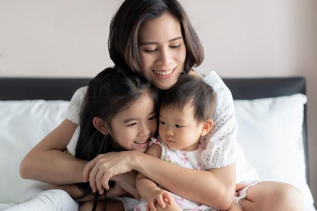 Linda mãe abraçando seus filhos com sorriso, sentado na cama no quarto.