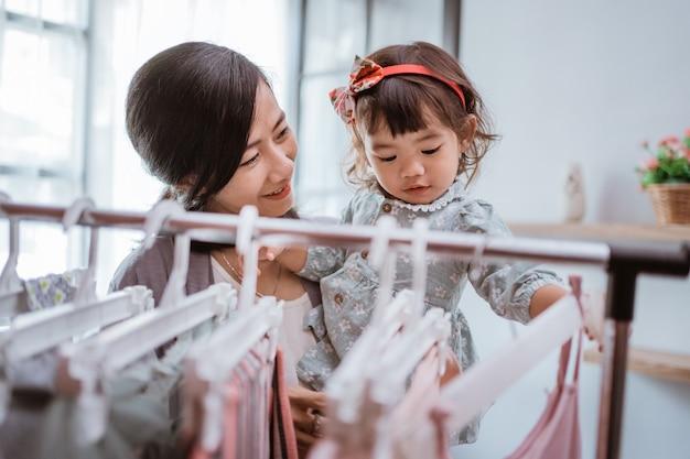 Linda mãe asiática levando a filha para comprar roupas