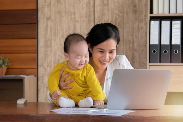 Linda mãe asiática passou tempo com curiosidade da criança bebê menino falando, brincando no local de trabalho em casa, adorável filho travesso feliz rindo com a mãe segura na mão, mãe solteira, alimentando a multi tarefa de trabalho