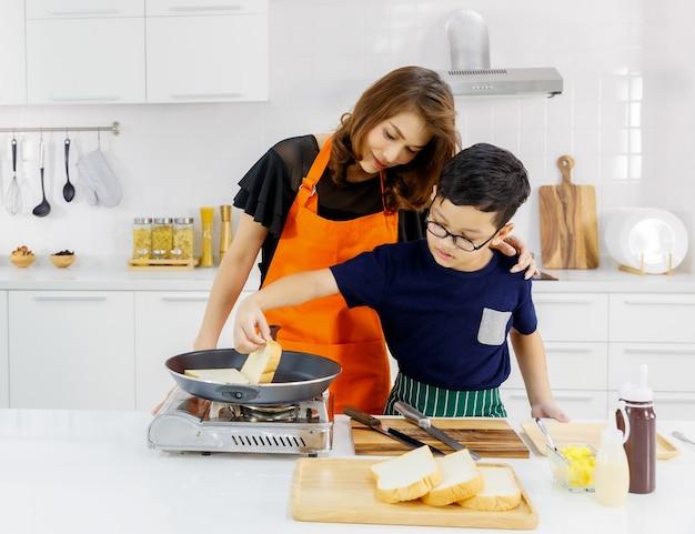Linda mãe asiática vestindo avental laranja abraça criança com amor na cozinha moderna de casa enquanto felizmente ensina o filho a assar pão na frigideira voadora como educação familiar para cozinhar comida saborosa.