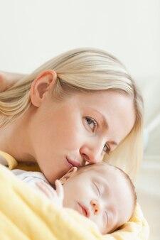 Linda mãe beijando seu bebê dormindo