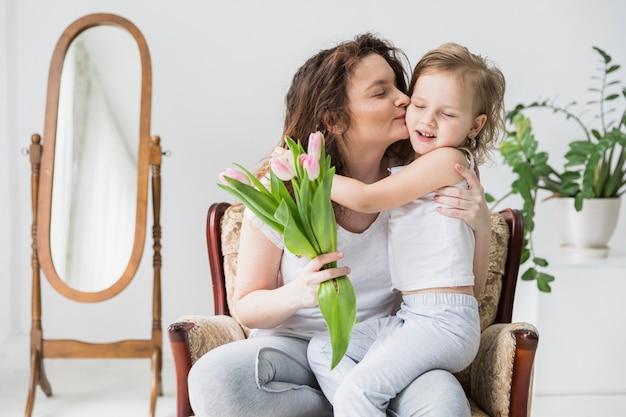 Linda mãe beijando seu filho em casa segurando o monte de flores de tulipa