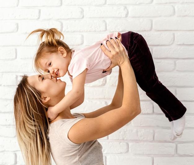 Linda mãe brincando com a filha em casa