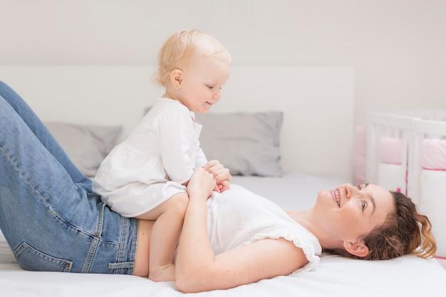 Linda mãe brincando com bebê fofo