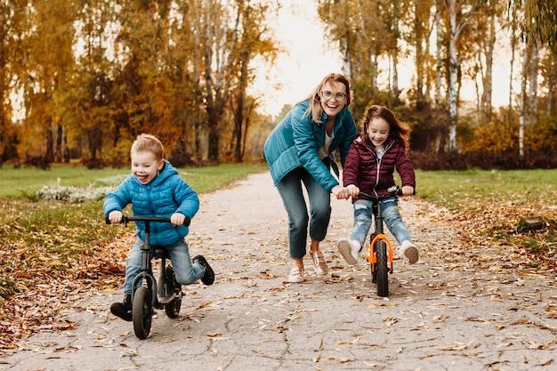 Linda mãe brincando com seus filhos enquanto inclina sua filha para andar de bicicleta enquanto seu filho vai na frente com a bicicleta rindo.