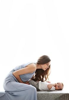 Linda mãe brincando olhando para seu filho, doce bebê moda modelo em vestido longo azul isolado
