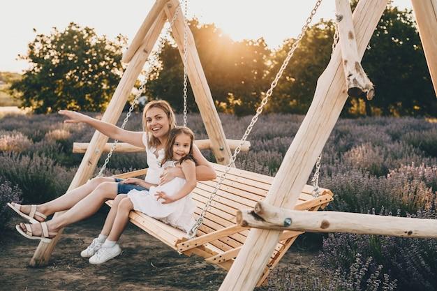 Linda mãe caucasiana e sua filha pequena sentadas em um balanço com um campo de lavanda no fundo