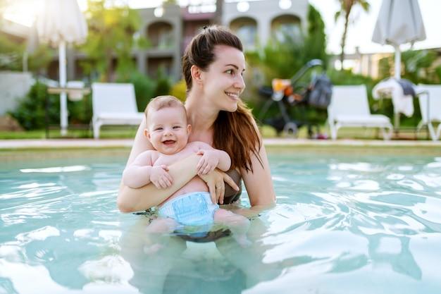 Linda mãe caucasiana em pé na piscina e segurando seu filho de 6 meses. bebê olhando para a câmera e sorrindo.