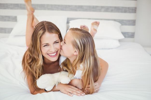 Linda mãe com a filha na cama