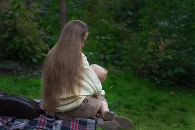 Linda mãe com cabelos longos amamenta seu bebê .vista traseira