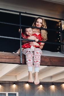 Linda mãe com filha em pijama de natal lendo livro na cozinha.