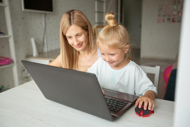 Linda mãe com filha está sentada em casa com o laptop