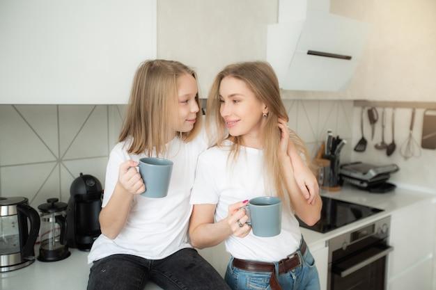 Linda mãe com filha na cozinha com canecas