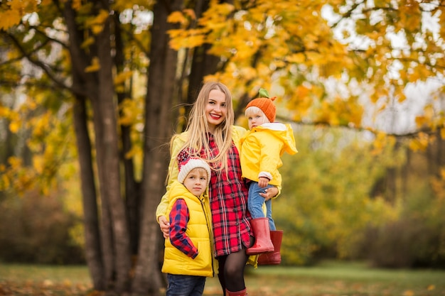 Linda mãe com filho e filha no parque outono