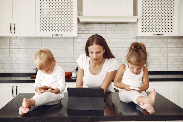 Linda mãe com filhos bonitos em casa em uma cozinha