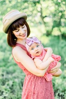 Linda mãe com o chapéu de palha e sua filha pequena família ao ar livre olhar em um vestido rosa. olhar de família. jovem mãe vomita bebê no céu, em dia ensolarado.