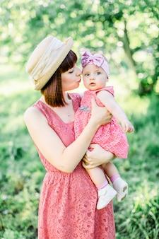 Linda mãe com o chapéu de palha e sua filha pequena família ao ar livre olhar em um vestido rosa. retrato ao ar livre de família feliz. olhar de família. mãe beija a filha em uma bochecha.