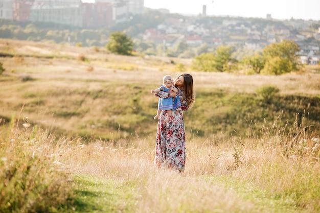 Linda mãe com sua filha bebê na mão está caminhando ao ar livre em um dia ensolarado.