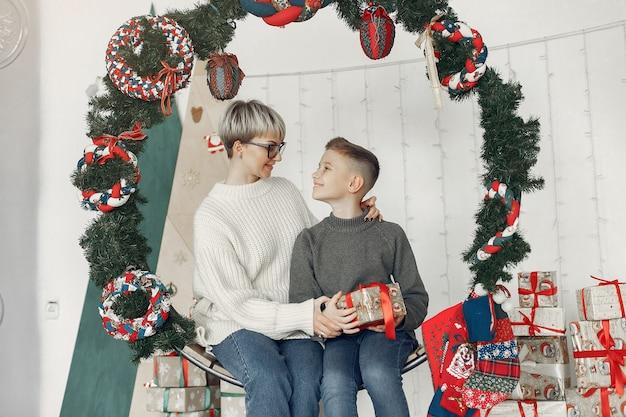 Linda mãe com um suéter branco. família em uma decoração de natal. menino em uma sala