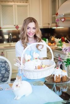 Linda mãe com uma cesta de bolos de páscoa nas mãos na cozinha.