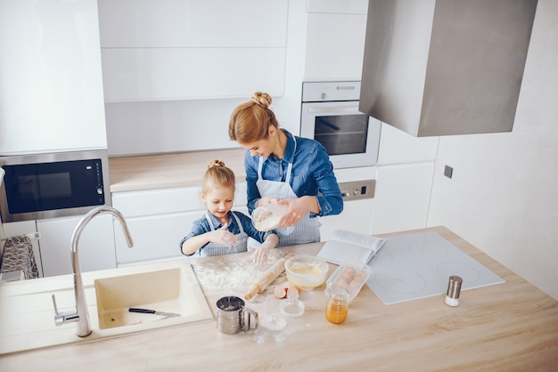 Linda mãe de camisa azul e avental está preparando o jantar em casa na cozinha
