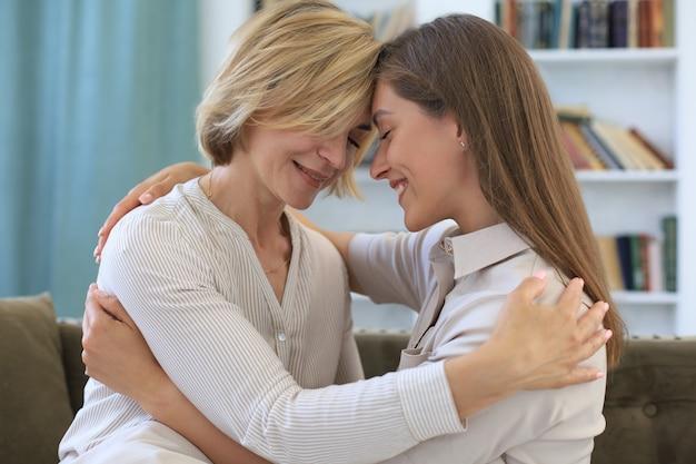 Linda mãe de meia-idade e sua filha adulta estão se abraçando e sorrindo enquanto está sentado no sofá em casa.