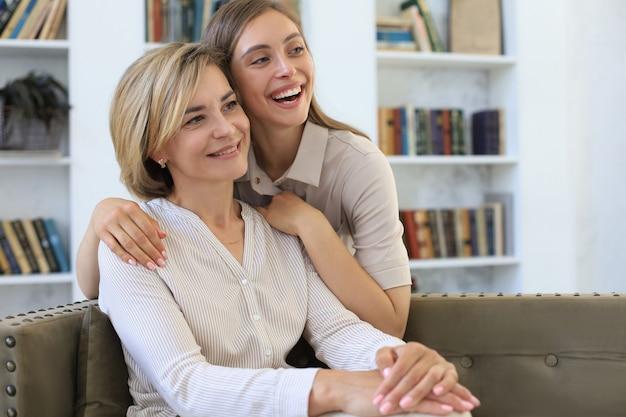 Linda mãe de meia idade e sua filha adulta estão se abraçando e sorrindo enquanto está sentado no sofá em casa.