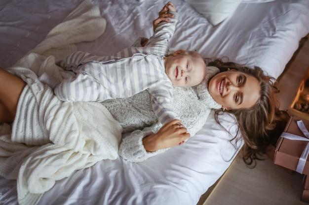Linda mãe de olhos azuis e o bebê deitado no quarto na cama na vista superior do lençol branco