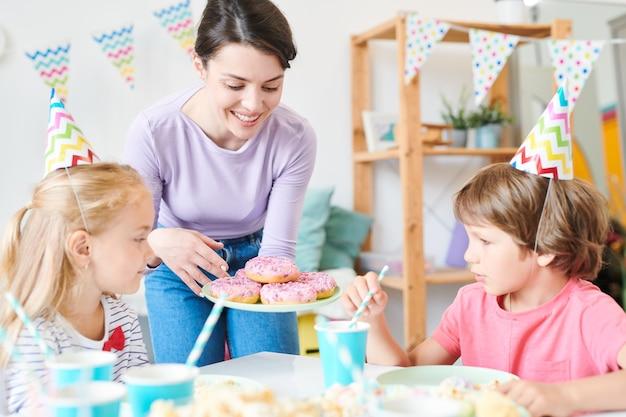 Linda mãe de uma das crianças segurando rosquinhas na mesa servida enquanto as mostra aos amigos na festa de aniversário