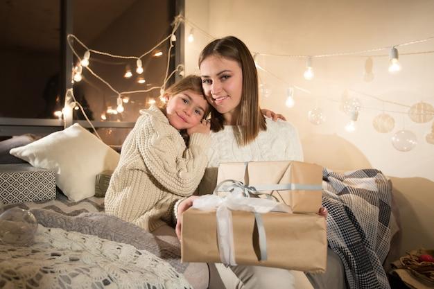 Linda mãe e filha abrindo um presente de natal mágico no interior aconchegante