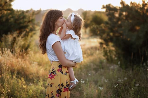 Linda mãe e filha brincando no campo