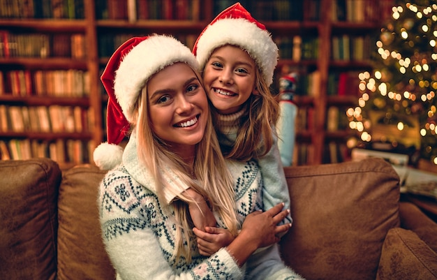 Linda mãe e filha, com chapéus de natal, luzes da árvore de natal. férias do retrato.
