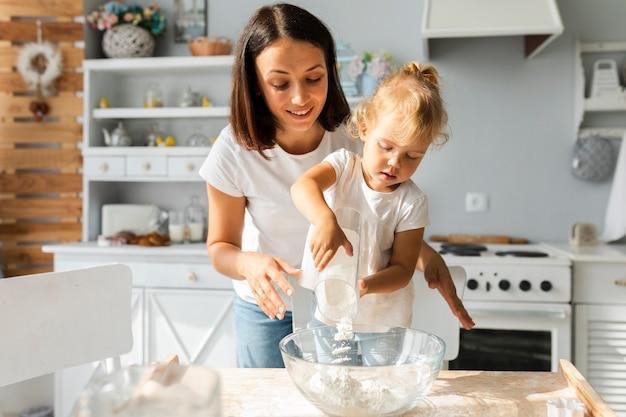 Linda mãe e filha cozinhando juntos