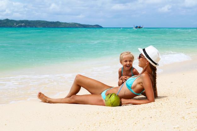 Linda mãe e filha deitar em trajes de banho na praia com areia branca e rindo
