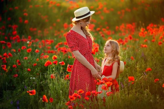 Linda mãe e filha em chapéus de palha e vestidos vermelhos se abraçam na primavera em um campo de papoulas nas montanhas.