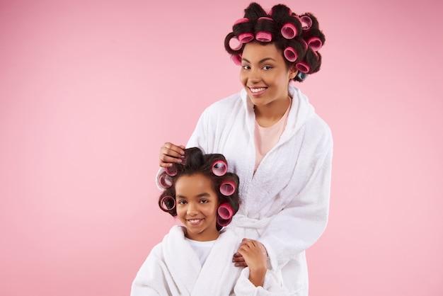 Linda mãe e filha em roupões de banho