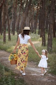 Linda mãe e filha em uma caminhada na floresta